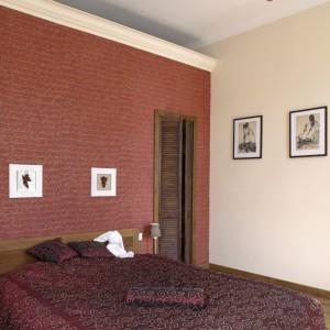 Buduar, w połowie którego można by przeprowadzić oś symetrii, został wytapetowany bordową tapetą z kaligraficznym wzorem. Podobny, nieco głębszy odcień ma narzuta i poduszki na wielkim, małżeńskim łóżku.  Fot. Monika Filipiuk.