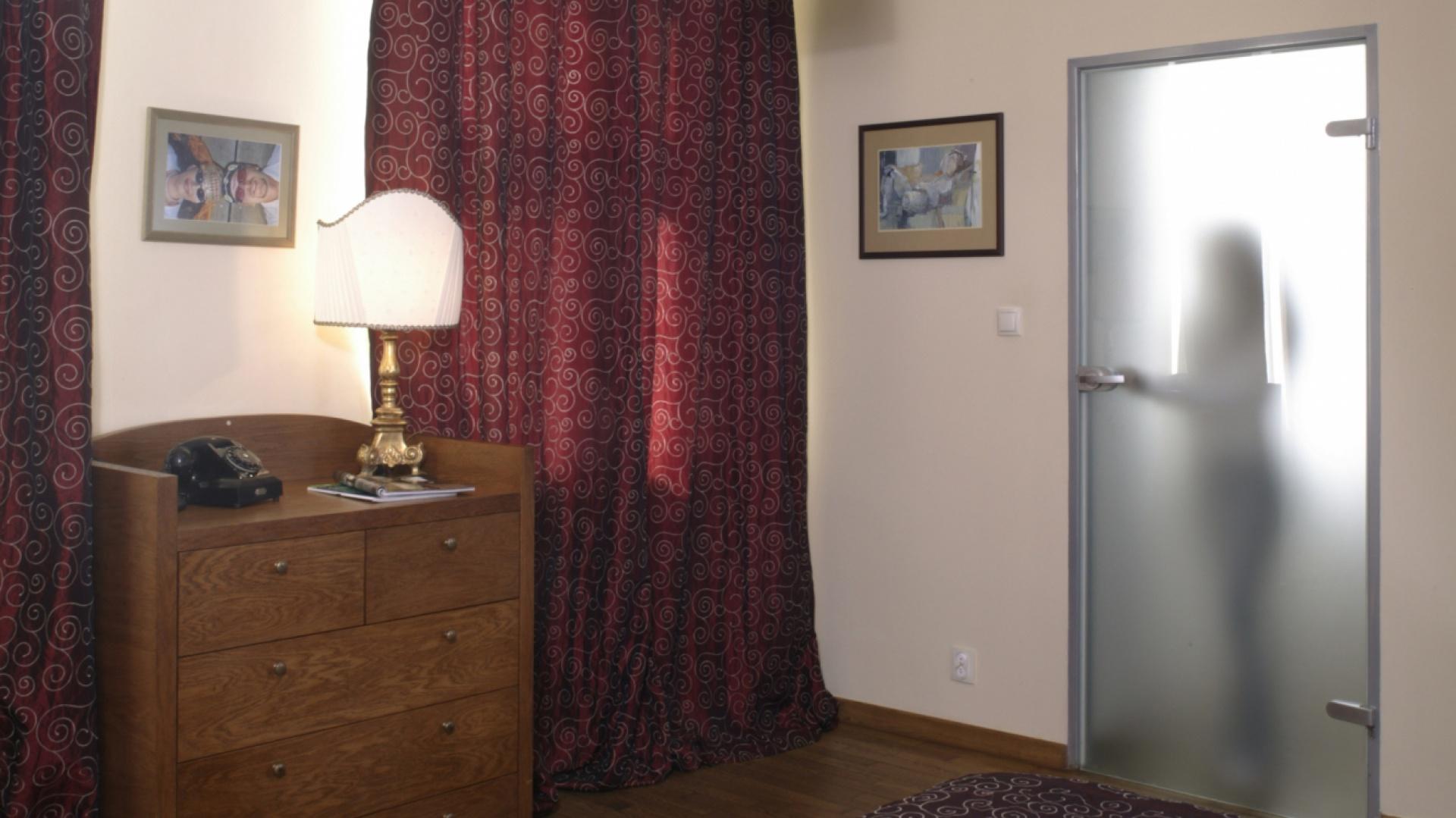 Dzięki dwóm, wysokim oknom, sypialnia jest bardzo jasna. By jednak zachować tu intymny nastrój, zawieszono w nich długie, ciężkie zasłony, z tej samej tkaniny, co narzuta na łóżko.  Fot. Monika Filipiuk.