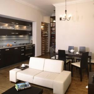 """Jasny, nowoczesny salon jest pełen smakowitych estetycznych """"kąsków"""". Wysokość wnętrza, oryginalny kominek, stylowe żyrandole i urokliwe starocie przypominają, że mieszkanie ma imponującą metrykę. Fot. Monika Filipiuk."""