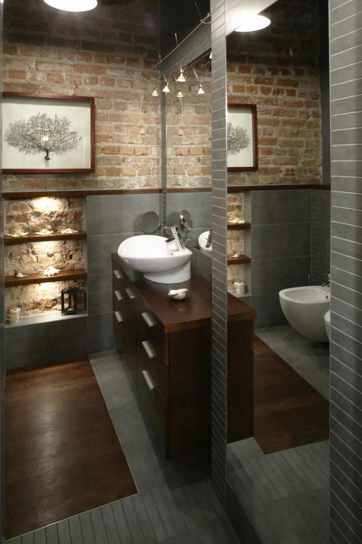 W łazience króluje egzotyczne drewno, gres w antracytowym kolorze, efektownie odsłonięte fragmenty ceglanej ściany i lustra, których zadaniem było optyczne powiększenie niedużej przestrzeni. Fot. Monika Filipiuk.