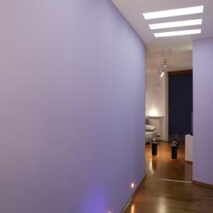 Korytarz, łączący się bezpośrednio z salonem, utrzymany jest w jasnofioletowym kolorze. Również tutaj dużą rolę odgrywa oświetlenie – drobne punkty świetlne nad podłogą oraz sufitowe świetlówki. Fot. Monika Filipiuk.