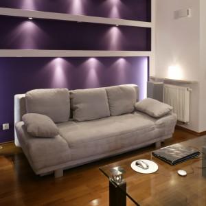 """Fioletowa barwa wykreowała w niewielkim salonie niepowtarzalny klimat, """"wzmocniony"""" przez kilka rzędów halogenowych światełek. Dzięki światłocieniowi, utworzyły one na ścianie nietypową dekorację, mieniącą się różnymi odcieniami fioletu. Fot. Monika Filipiuk."""