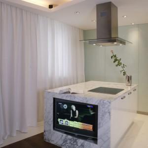 Wyspa kuchenna jest obudowana białym marmurem, z szarym rysunkiem.  Wbudowany w nią telewizor to odważny i zaskakujący pomysł. Fot. Monika Filipiuk.