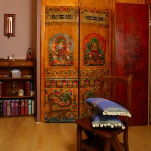 Dzięki pojemnej szafie sypialnię można traktować również jako pokój garderobiany. Na wykonanych ze starego parawanu drzwiach mebla, widnieje wizerunek tybetańskich królów. Fot. Monika Filipiuk.