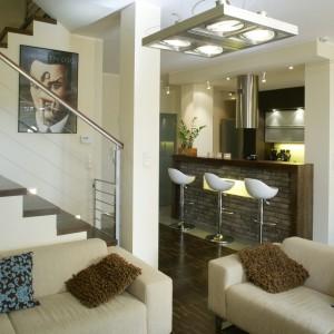 """Widoczne po lewej schody (nad nimi oniryczny plakat Olbińskiego) prowadzą do bardziej prywatnej części domu. Ich stopnie wykonane są z tego samego materiału, którym wyłożono podłogę w salonie, czyli z czarnego dębu przemysłowego z charakterystycznymi jaśniejszymi """"nitkami"""". Fot. Monika Filipiuk."""