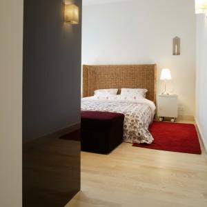 """Do sypialni prowadzi """"tunel"""" utworzony przez garderobianą szafę. Czerwony puszysty dywan, umieszczony przy łóżku, umili poranne wstawanie. Fot. Monika Filipiuk."""