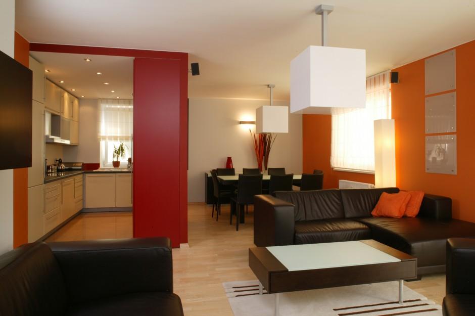 Dwustronna, ciemnoczerwona konstrukcja, z jednej strony stanowi ścianę salonu, z drugiej zaś stała się częścią zabudowy kuchennej. W duecie z pomarańczową ścianą zamieniła pomieszczenie w bardzo energetyczne miejsce. Fot. Bartosz Jarosz.