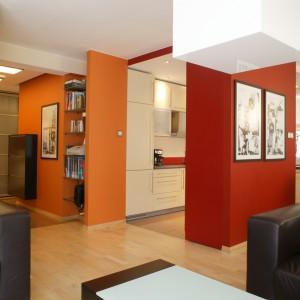 Soczysta barwa z salonu powtarza się w części przechodniej mieszkania. Ciepłe nuty pomarańczy korespondują tutaj z kuchenną zabudową oraz ciemnobrązowymi meblami. Fot. Bartosz Jarosz.