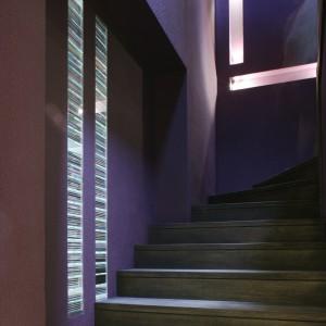 Chłodny i tajemniczy. Taki klimat klatki schodowej wykreowano za pomocą światła i intensywnego fioletu na ścianach. Światło sączy się z salonu przez podłużne wnęki. Masywne, dębowe schody nadają temu miejscu nieco mroczny, intrygujący charakter. Fot. Monika Filipiuk.