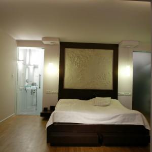 Wielkie łoże zostało ozdobione okazałym zagłówkiem, w którym umieszczono oryginalną płaskorzeźbę. Po obu stronach łóżka znajdują się bliźniacze, wiszące lampki nocne oraz drzwi prowadzące do łazienki i garderoby. Fot. Monika Filipiuk.