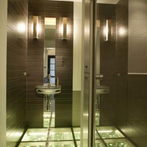Oprócz podłogi, w łazience świecą także kinkiety Axo umieszczone po obu stronach wysokiego, od sufitu do podłogi, wąskiego lustra. Po prawej stronie znajduje się ukryta za transparentną szybą wahadłowych drzwi, wnęka prysznicowa. Fot. Monika Filipiuk.