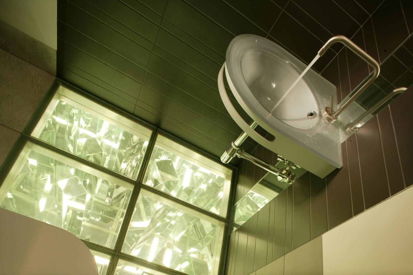 Nowoczesne wyposażenie i detale podkreślają industrialny charakter łazienki: metaliczna armatura Isystick (Zucchetti), szklana umywalka Smart (Logo Design) oraz lśniące płytki ceramiczne, między które zostały wmontowane prawie niewidoczne, minimalistyczne szafki. Fot. Monika Filipiuk.
