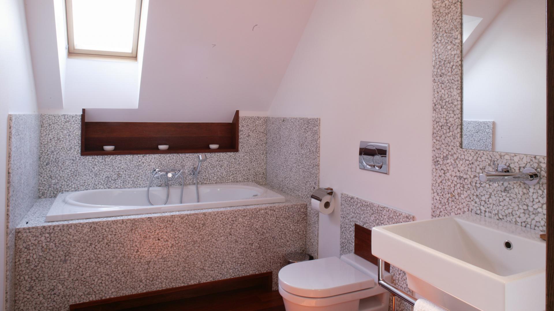 Najbardziej wyrazistym elementem łazienki  jest okładzina ścienna. Choć  płytki z otoczaków zatopionych w przezroczystej żywicy pokrywają zaledwie fragmenty ścian, mimowolnie skupiają na sobie uwagę. Fot. Monika Filipiuk.