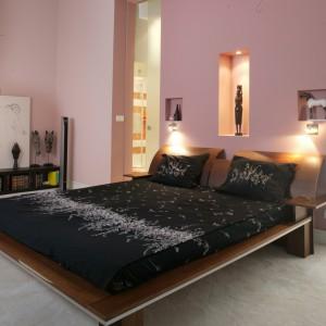 Orzechowe łóżko z wydatnymi zagłówkami jest ozdobione aluminiową wstawką. Towarzyszy mu niska, także ciemnobrązowa szafka z książkami, służąca za podstawę dla obrazu czy masek w postaci głów zwierząt.