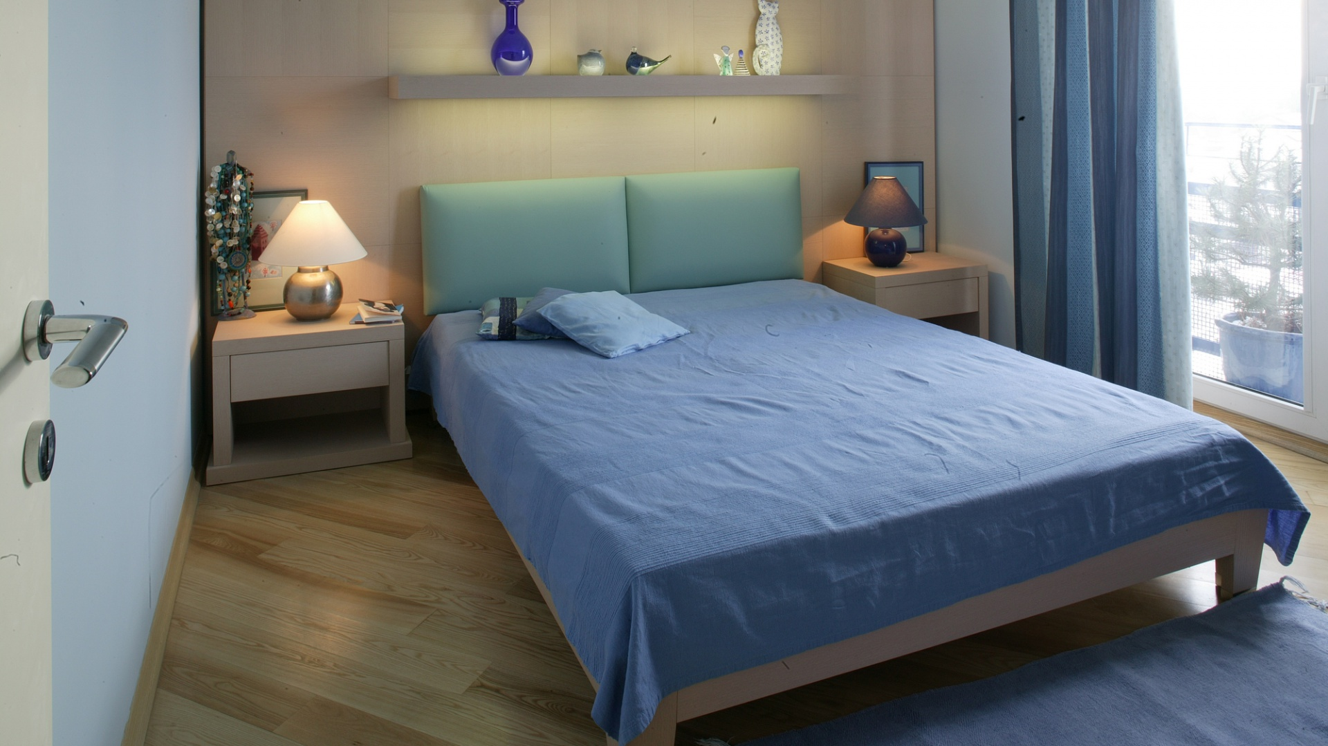 Niebieski pozostaje w delikatnym kontraście do piaskowej bieli mebli i panelu zainstalowanego za wezgłowiem łóżka. Fot. Marcin Onufryjuk.