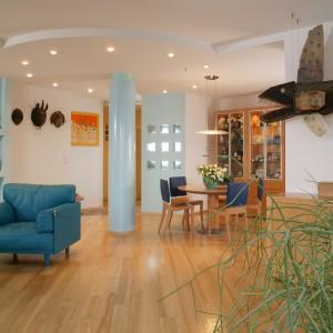 Przestrzeń salonu i jadalni symbolicznie oddziela błękitna kolumna, pokryta stiukiem. Fot. Marcin Onufryjuk.