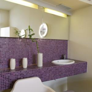 Blat pod umywalką, i przylegającą do niego ścianę, wykończono mozaiką z kolekcji Legenne firmy Bisazza. W kostkach mozaiki znajduje się złota nić, sprawiająca że szkło skrzy się refleksami. Fot. Monika Filipiuk.