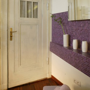 Drzwi łazienkowe zostały pobejcowane na biało. Stołeczek z wrzosową poduszką to kolejny element kolekcji Tapas. Fot. Monika Filipiuk.