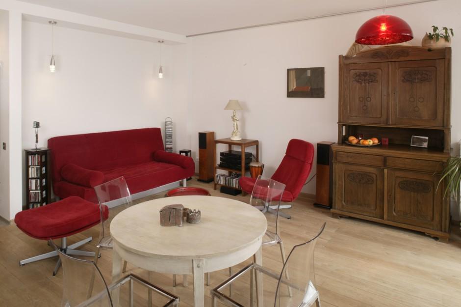 Wystarczy jedno krótkie spojrzenie i wiemy na pewno, że to czerwień dominuje w tym wnętrzu. Jest silnie reprezentowana przez sofę, obrotowy fotel i podnóżek (IKEA), okrągły stolik kawowy oraz wiszącą lampę. Fot. Monika Filipiuk.
