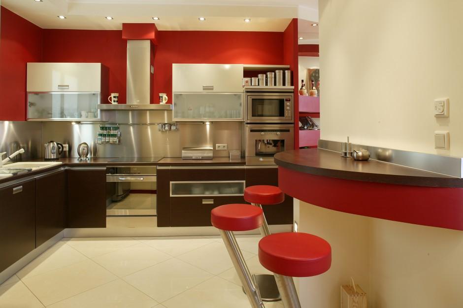 Nowoczesna kuchnia jest jednocześnie ciepła w odbiorze. Dominującą czerwień neutralizuje stonowana kolorystyka podłogi. Barowe stołki z siedziskami z czerwonej skóry idealnie uzupełniają wnętrze. Fot. Marcin Łukaszewicz.