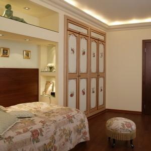 W romantycznej, kobiecej sypialni, najważniejsza jest specjalnie zaprojektowana zabudowa, w której obrębie znalazło się łóżko, szafki z sosnowego, pobejcowanego na ciemną wiśnię drewna, podświetlane nisze i pojemna szafa. Fot. Monika Filipiuk.