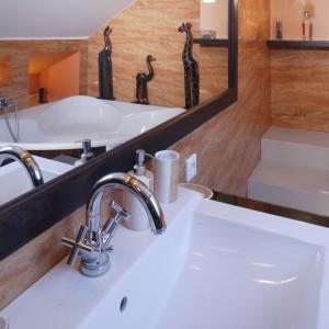 Białe bryły ceramiki łazienkowej doskonale harmonizują z ciepłą kolorystyką wnętrza. Ogromne lustro nad umywalką optycznie podwaja przestrzeń, wzmacniając tym samym wrażenia estetyczne. Fot. Monika Filipiuk.