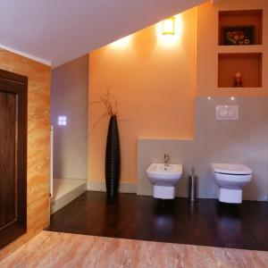 W miejscu dawnego WC architekt zaprojektował kabinę prysznicową, co pozwoliło wykorzystać uzyskaną przestrzeń do maksimum. Ścianę za sedesem i bidetem obudowano jasnoszarymi płytkami. Ten sam materiał został wykorzystany do budowy schodów przy wannie. Fot. Monika Filipiuk.