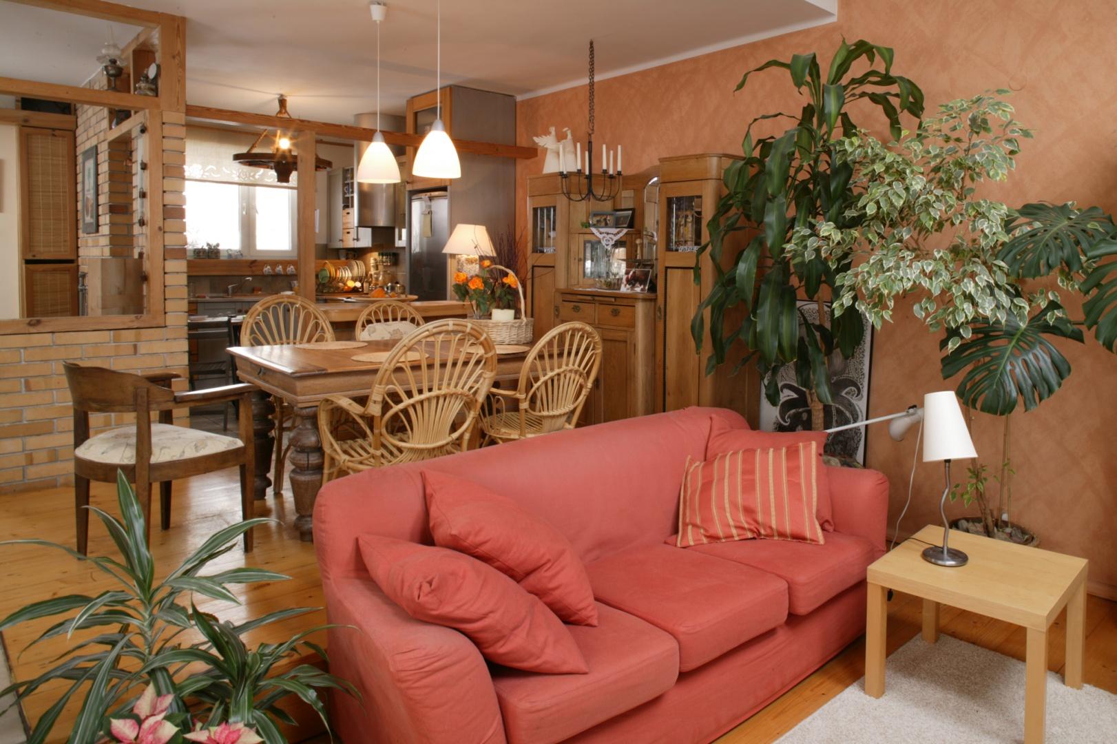 Salon i jadalnia zostały urządzone w ciepłych barwach. Ceglastym ścianom towarzyszy sofa z IKEI i naturalne barwy drewnianych dodatków. Fot. Monika Filipiuk.