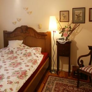 """Wezgłowie łóżka to fragment starej, zabytkowej szafy, """"zaadoptowanej"""" na potrzeby sypialni. Komponuje się z nim jasna, kwiecista pościel. Fot. Monika Filipiuk."""