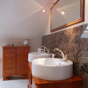 Łazienka została wyłożona jasnobeżowym marmurem berecia, natomiast ciemnobrązowe tafle wykorzystano jako tło do wyeksponowania szafki z umywalkami. Fot. Tomasz Markowski.