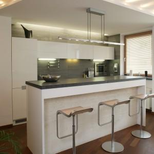 Centralną częścią kuchni jest bar otoczony krzesłami. Zasłania on niezbędną, ale nie najważniejszą strefę przestrzeni – miejsce przygotowywania posiłków – jedynie zaplecze towarzyskich spotkań. Fot. Marcin Łukaszewicz.