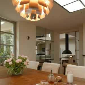 Wnętrze pomimo oszczędnej linii mebli, jasnoszarej, zimnej kolorystyki emanuje elegancją, a także ciepłem, którego źródłem jest nie tylko kominek, ale także drewno wykorzystane do wykonania podłóg i stołu oraz światło, wydobywające się z licznych lamp. Fot. Tomasz Markowski.