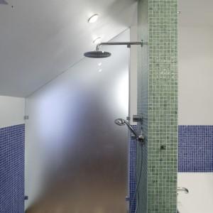 Kabinę prysznicową od sypialni oddziela ścianka z mlecznego szkła, tworząc ciekawy efekt wizualny w obu pomieszczeniach. Fot. Bartosz Jarosz.
