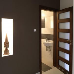 Dekoracyjny element w holu: ścianka pomalowana na ciemny brąz. W podświetlonej wnęce ustawiono oryginalną afrykańską rzeźbę. Fot. Bartosz Jarosz.