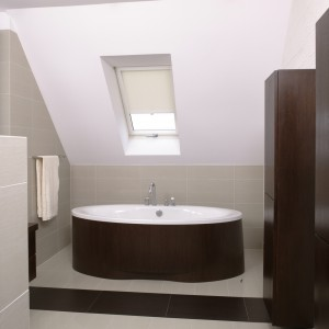 Centralnym punktem łazienki jest wanna o opływowym kształcie, dekoracyjnie obudowana drewnem wengé. Fot. Bartosz Jarosz.