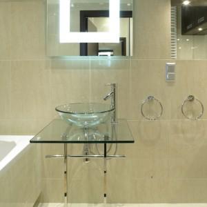 """Dobór lekkich, przezroczystych detali, znakomicie """"odciążył"""" wnętrze łazienki, praktycznie w całości pokryte kamieniem. Oryginalnie podświetlone kwadratowe lustro oraz szklana umywalka na szklanym blacie. Fot. Bartosz Jarosz."""