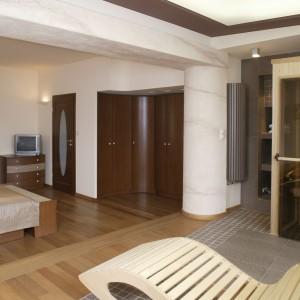 """Obok standardowych elementów wyposażenia – łóżko, szafa, szafki itd., w tej sypialni znalazła się... sauna. W tym kontekście drewniany fotel-leżak to już tylko stylistyczno-funkcjonalna kropka nad """"i"""". Fot. Monika Filipiuk."""