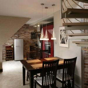 Jadalniany stół i krzesła z wysokimi oparciami stoją naprzeciw salonu i jednocześnie w bezpośrednim sąsiedztwie otwartej kuchni. Fot. Bartosz Jarosz.