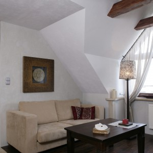 Większość zgromadzonych przez lata mebli, m.in. kanapa, tapicerowana alcantarą w kolorze ciepłego beżu, pochodzi ze składu kolonialnego Inne Meble. Fot. Bartosz Jarosz.