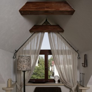 Umieszczone między sufitowymi skosami okno, to istotny i bardzo dekoracyjny element mieszkania. Wykonany z piaskowca parapet ma dość nietypowe boki, tworzące ekspozycyjny blat. Fot. Bartosz Jarosz.