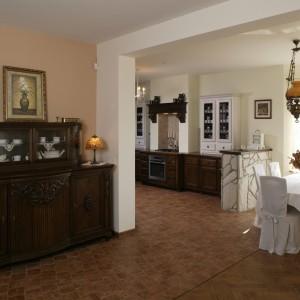 """Stojąca u wejścia do kuchni przepiękna komoda z rzeźbieniami i kryształowymi witrynami, została """"upolowana"""" na targu staroci."""
