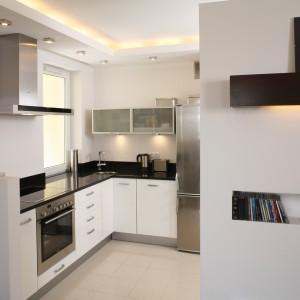 Kuchnia została urządzona meblami z białego, lakierowanego mdf-u (BRW), ze stalowymi wykończeniami i czarnymi, granitowymi blatami roboczymi. Do tego dobrano minimalistyczne wyposażenie. Fot. Bartosz Jarosz.