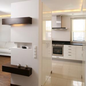 Dwie wysokie, ustawione na przeciwko siebie kuchenne szafy, zostały specjalnie doprojektowane i wykonane, podobnie jak reszta mebli, z białego lakierowanego mdf-u. Jedną z szaf wbudowano pomiędzy efektowne, pełniące głównie dekoracyjną rolę, ścianki. Fot. Bartosz Jarosz.