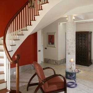 """Holl jest zapowiedzią stylistyki pozostałej części domu. Biała wstęga schodów została wyeksponowana na tle """"ostrej"""", pomidorowej ściany. To stylistyczny skrót i zarazem wstęp do tego, na co natkniemy się dalej. Fot. Bartosz Jarosz."""
