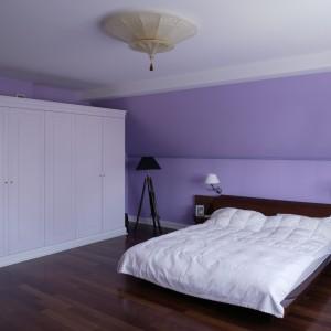 Sypialnia, dzięki ograniczaniu sprzętów do minimum, to przestrzeń pełna oddechu. Na fioletowym tle ścian, wyraźnie zaznacza się łóżko z czekoladowego drewna i lampa (Almi Decor) na trzech drewnianych nogach. Fot. Bartosz Jarosz.