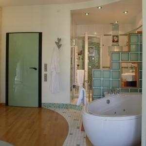 Wydzielona strefa łazienkowa ma własną, mozaikową podłogę. Postument jest tyle dekoracyjny co użyteczny – pozwala zmieścić wodne instalacje. Fot. Bartosz Jarosz.