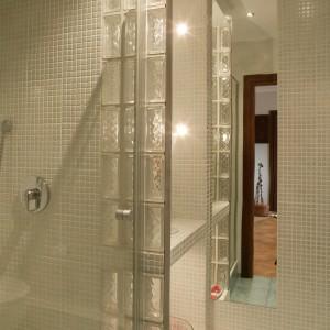 Wąski i długi pas lustra wklejony między płytkami podwaja przestrzeń i podświetlane wnęki. To jeden z zabiegów optycznego powiększenia małej łazienki. Fot. Tomek Markowski.