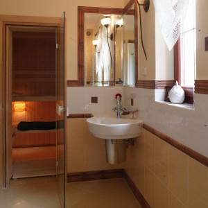 Fińska sauna ze świerku jest częścią łazienki. Narożną umywalkę wieńczy, także narożne, lustro, intrygująco powielające przestrzeń w nieskończoność.  Fot. Monika Filipiuk.