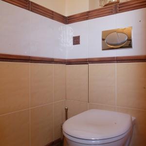 Sedes ukryty jest we wnęce za kabiną. Ściany, tak jak w pozostałej części łazienki, przecinają ceramiczne listwy, stylizowane na rzeźbione drewno.  Fot. Monika Filipiuk.