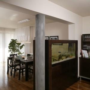 Akwarium wraz z obudową tworzy rodzaj ścianki oddzielającej część kuchenną od jadalni i salonu. Widoczne z obu stron jest oryginalnym elementem aranżacji. Fot. Bartosz Jarosz.